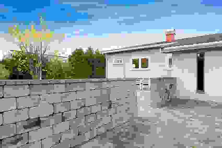 Flotte detaljer utomhus med stein i gårdsplass, steinmur og pusset del av fasaden