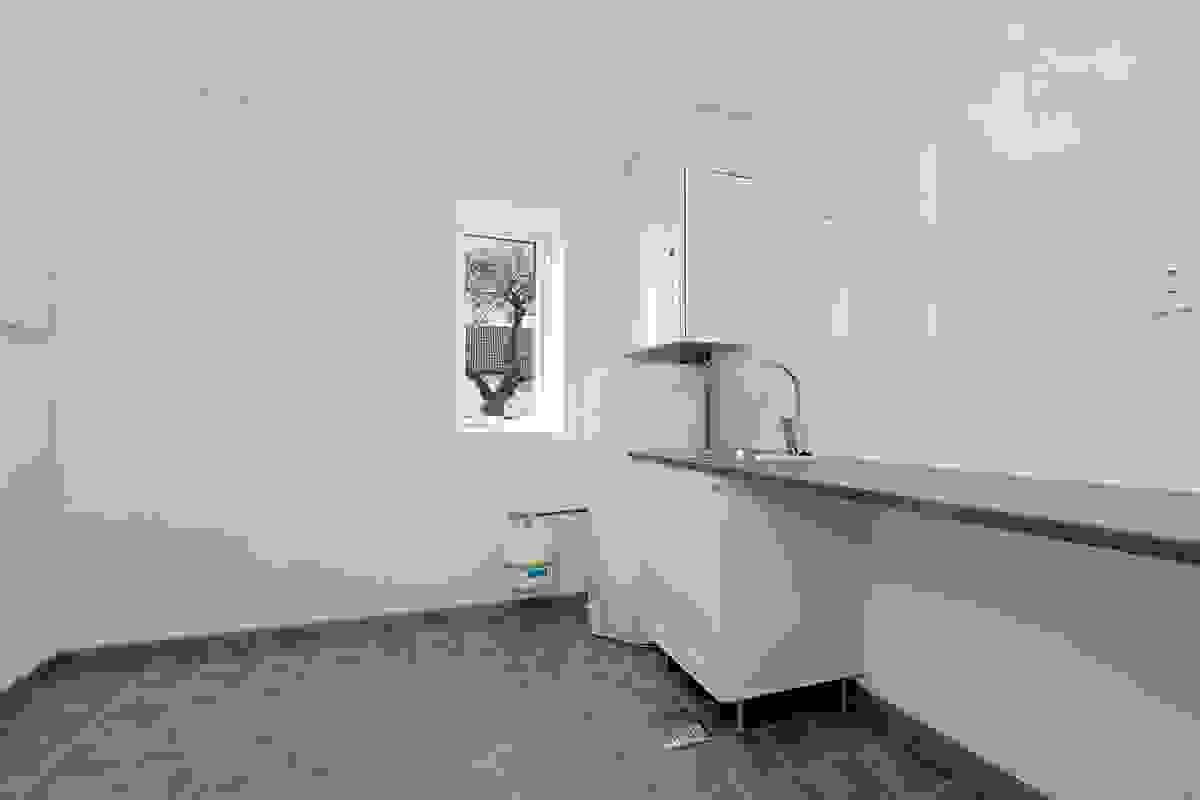 Et superpraktisk vaskerom er innredet med utslagsvask, brettebenk, varmtvannsbereder, opplegg for vaskemaskin og ventilasjonsmotor