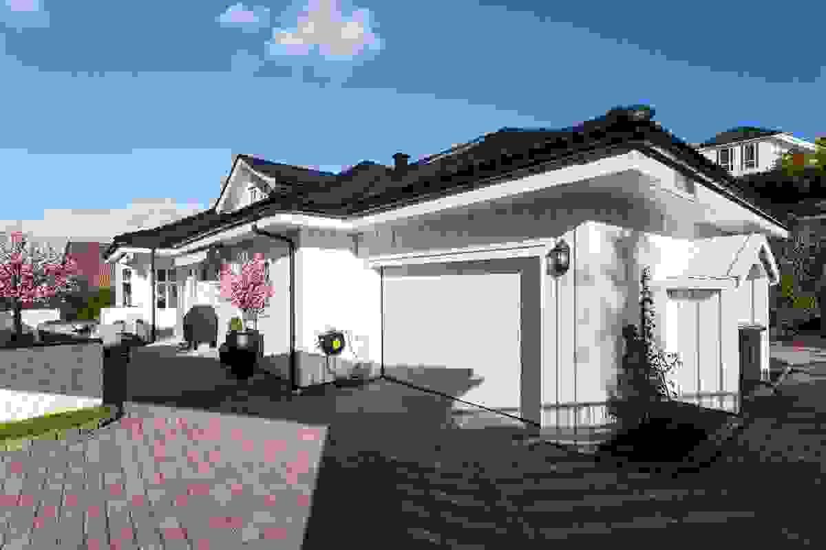 Fasaden mot vest med integrert garasje og stor steinlagt gårdsplass nærmest i bildet