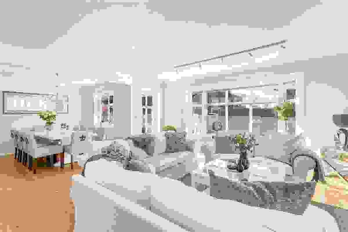 Stue og spisestuen har store vinduer mot vest som vender ut mot den usjenerte hagen