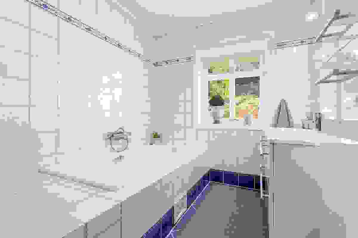 Baderommet i 1. etasje ligger innerst i soveromsgangen og har praktisk inngang både fra denne og fra husets hovedsoveværelse
