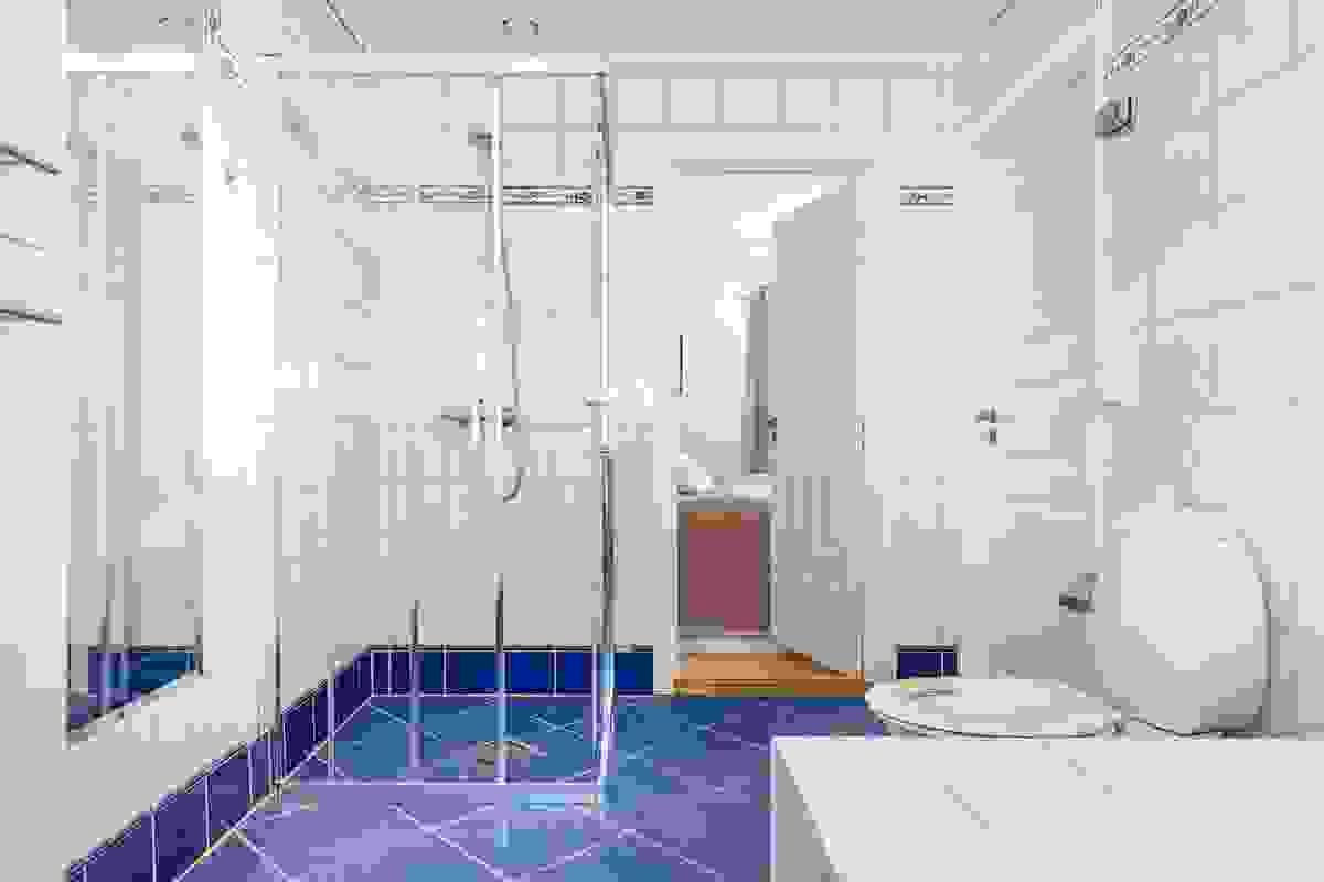 e lyse og sjøblå flisene på gulvet matcher fint til de hvite veggflisene