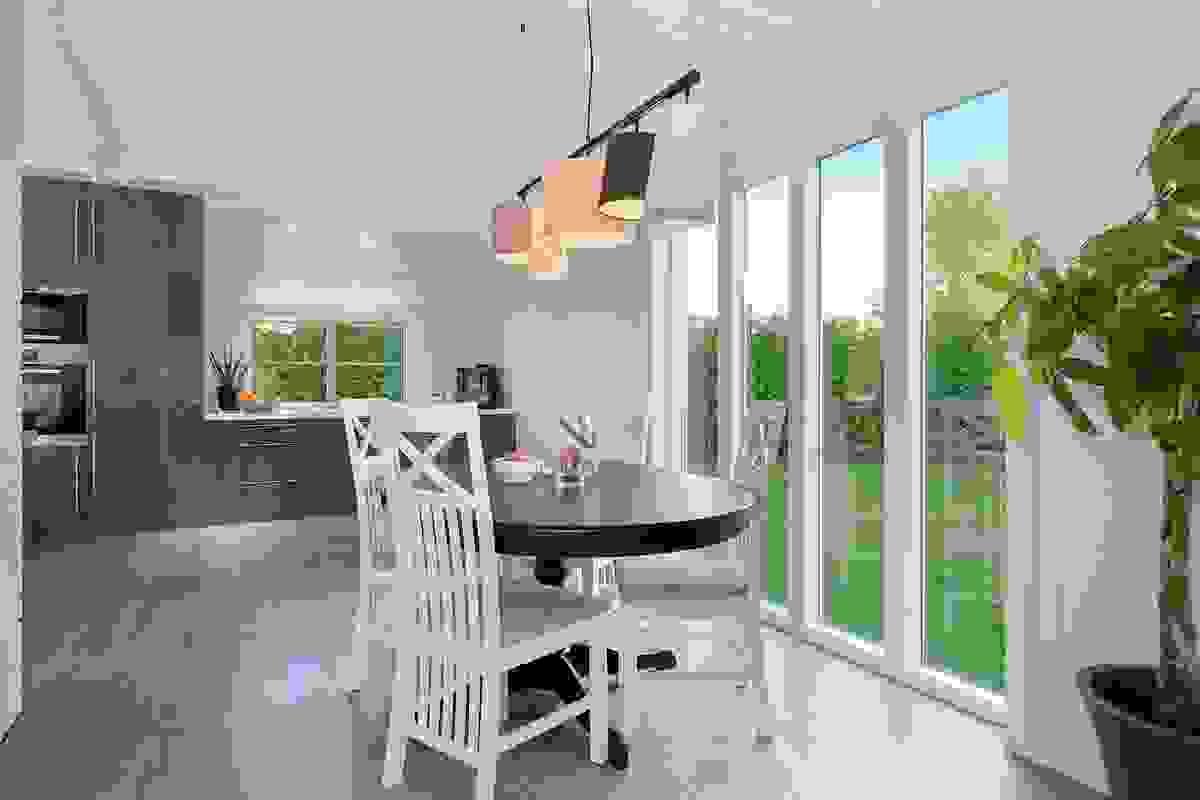 Spisestue med tak til gulv vinduer som slipper inn masse lys