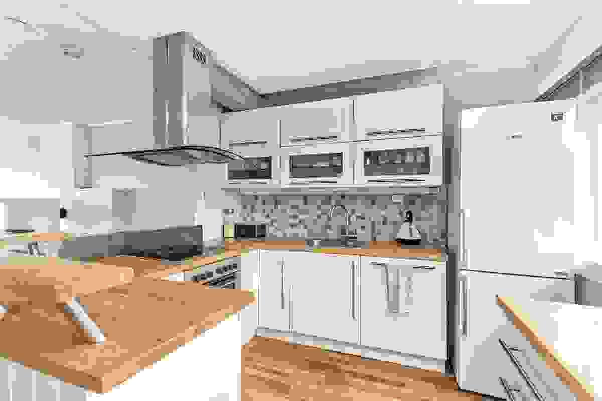 Lyse fronter med moderne profiler og heltre benkeplater. Av integrerte hvitevarer er det; komfyr, keramisk platetopp og oppvaskmaskin.