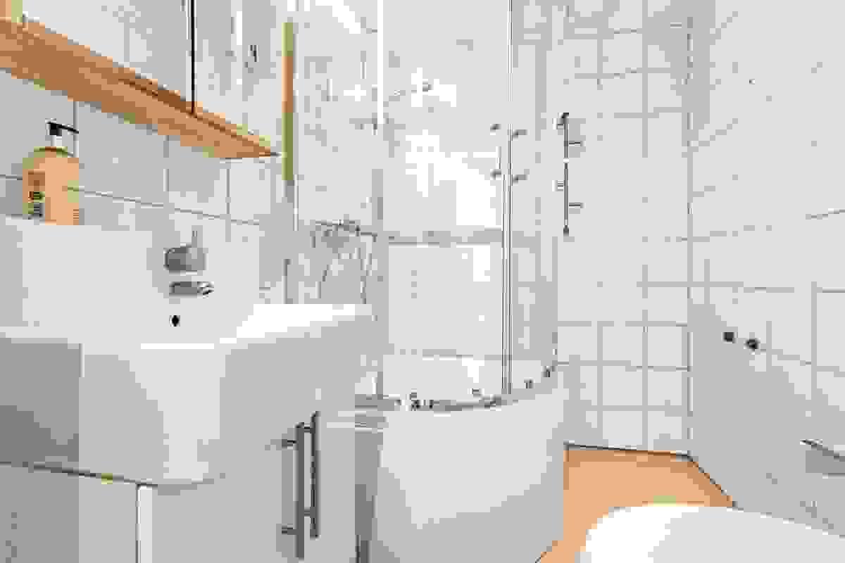 Badet i 1. etasje har belegg på gulv og flis på vegger. Innredningen består av servant på innredning med to underskap, speilskap og lysarmatur. Videre er det dusjkabinett (nytt i 2018), sokkeltoalett.