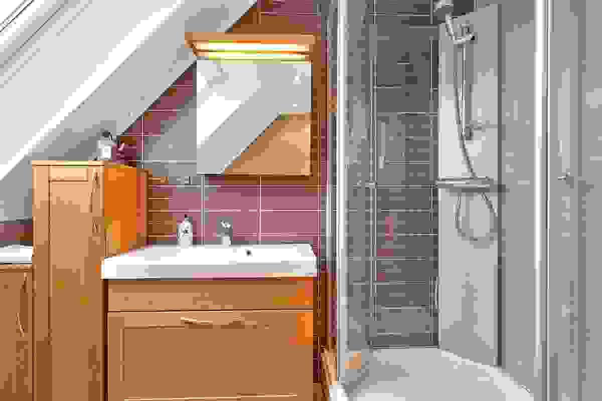 Badet i 2. etasje fremstår moderne med fliser på vegger og gulv. Varmekabler i gulvet gir deilig temperatur året rundt.