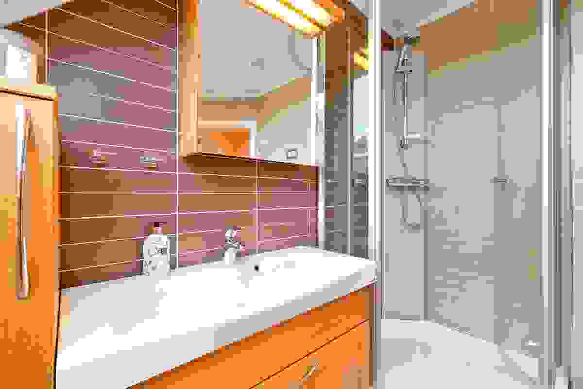 Baderomsinnredningen består av servant nedfelt i innredning med en stor skuff, to sideskap og speilskap med overlys. Videre er det veggehengt toalett, dusjkabinett og badekar