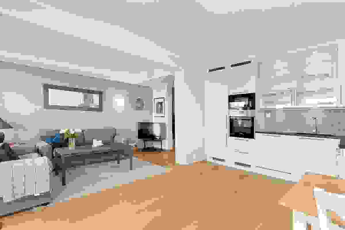 """Kjøkkeninnredningen blir nærmest som et """"møbel i stuen"""" med sin plassbygde løsning og takhøye overskap som gir inntrykk av """"håndsøm"""" til rommet."""