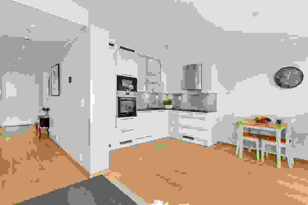 Den åpne løsningen mot leilighetens brede gang gir også ekstra romfølelse til oppholdsarealet i stuen