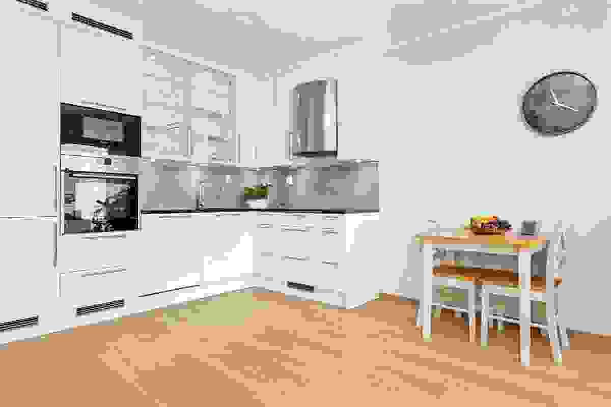 Det lekre kjøkkenet har innredning i hvit utførelse fra møbelprodusjenten Arens med rektangulære fronter med speildører