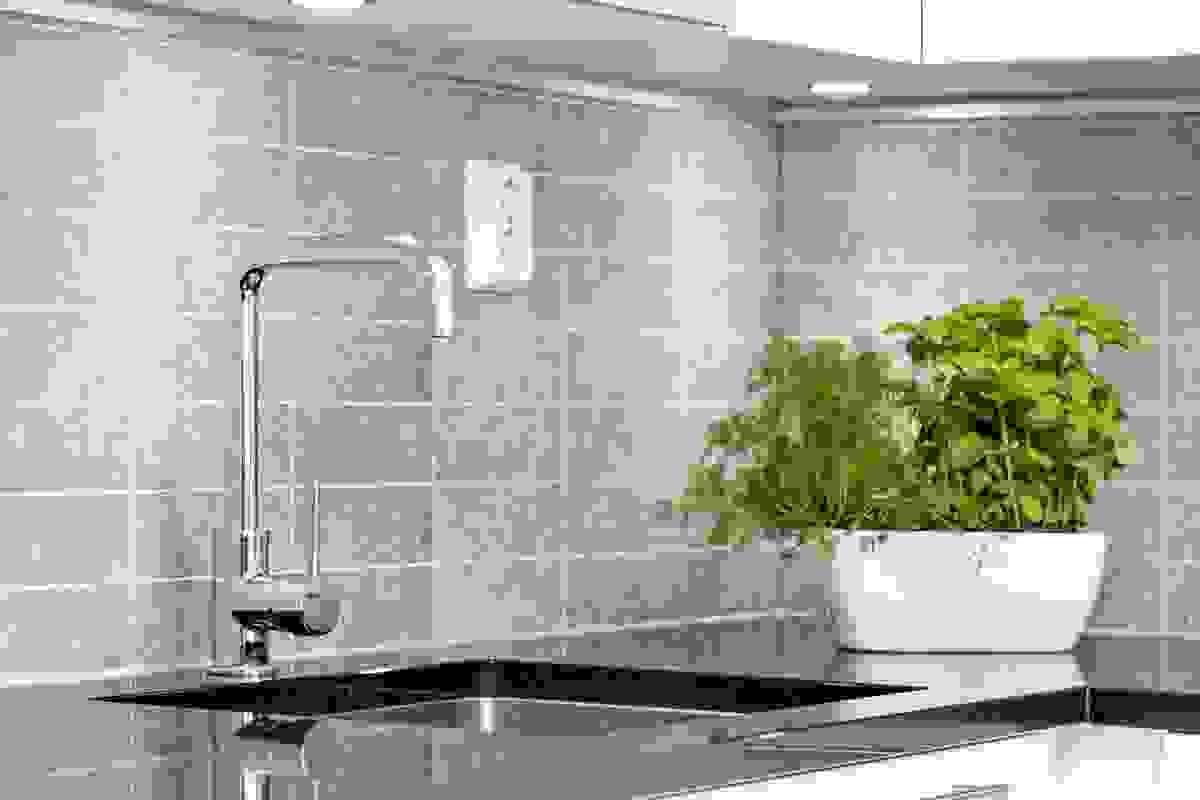 Det er lagt Kitchenboard panelplater mellom benker og overskap