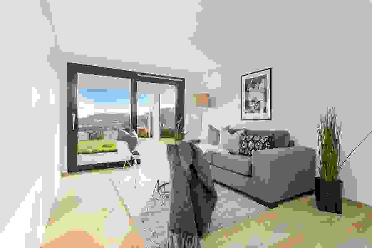 Den store skyvedøren med glass fra gulv til tak fyller rommet med dagslys og ikke minst utsikt