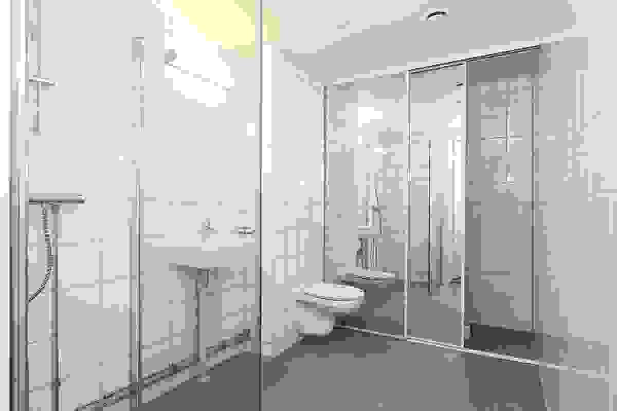 Flislagt bad/vaskerom med WC, servant, dusj samt speilskyvedør til vaskeromsdel