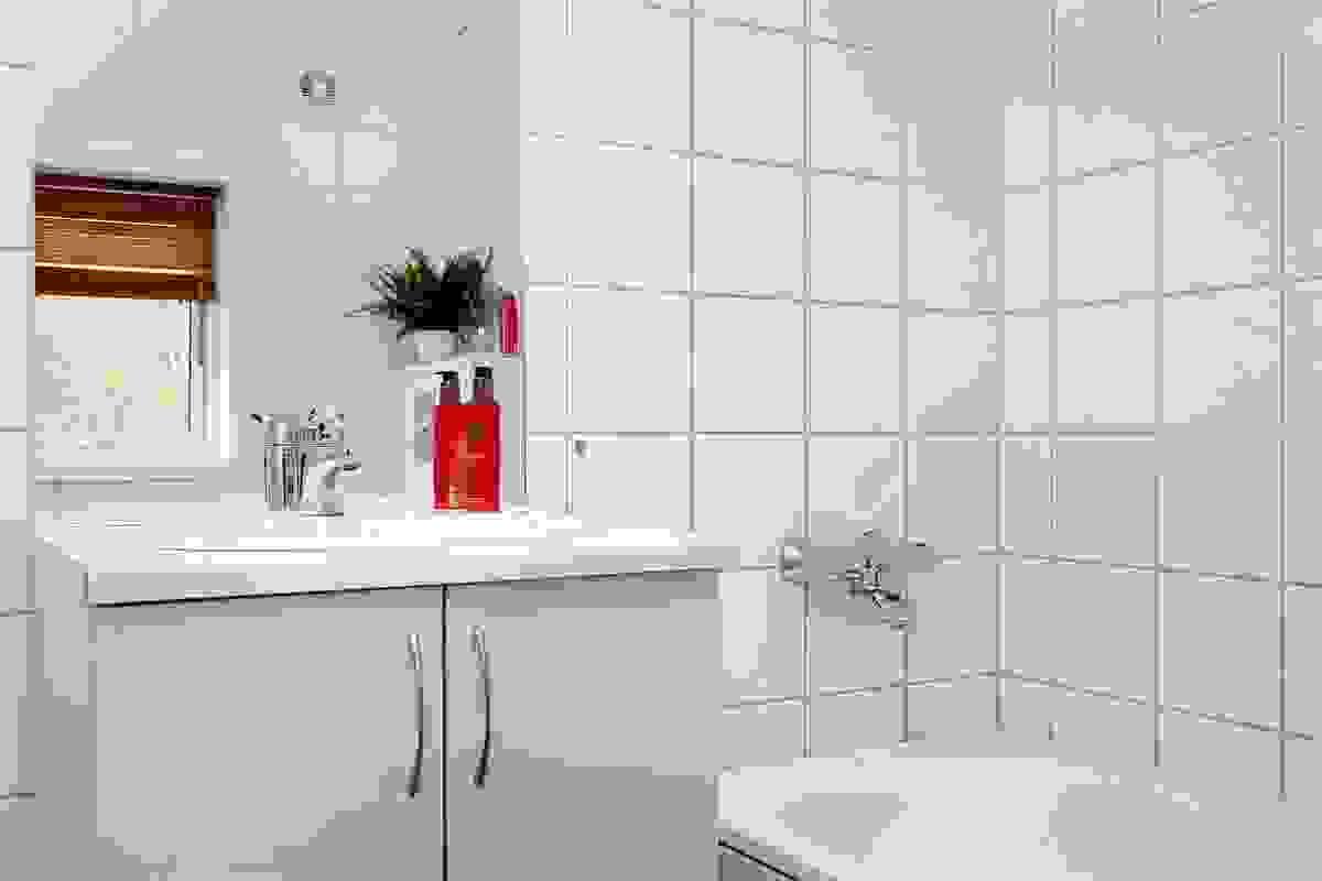 Badet er innredet med vegghengt toalett og dusjhjørne med glassdører. Videre er det utslagsvask og opplegg for vaksemaskin og tørketrommel.