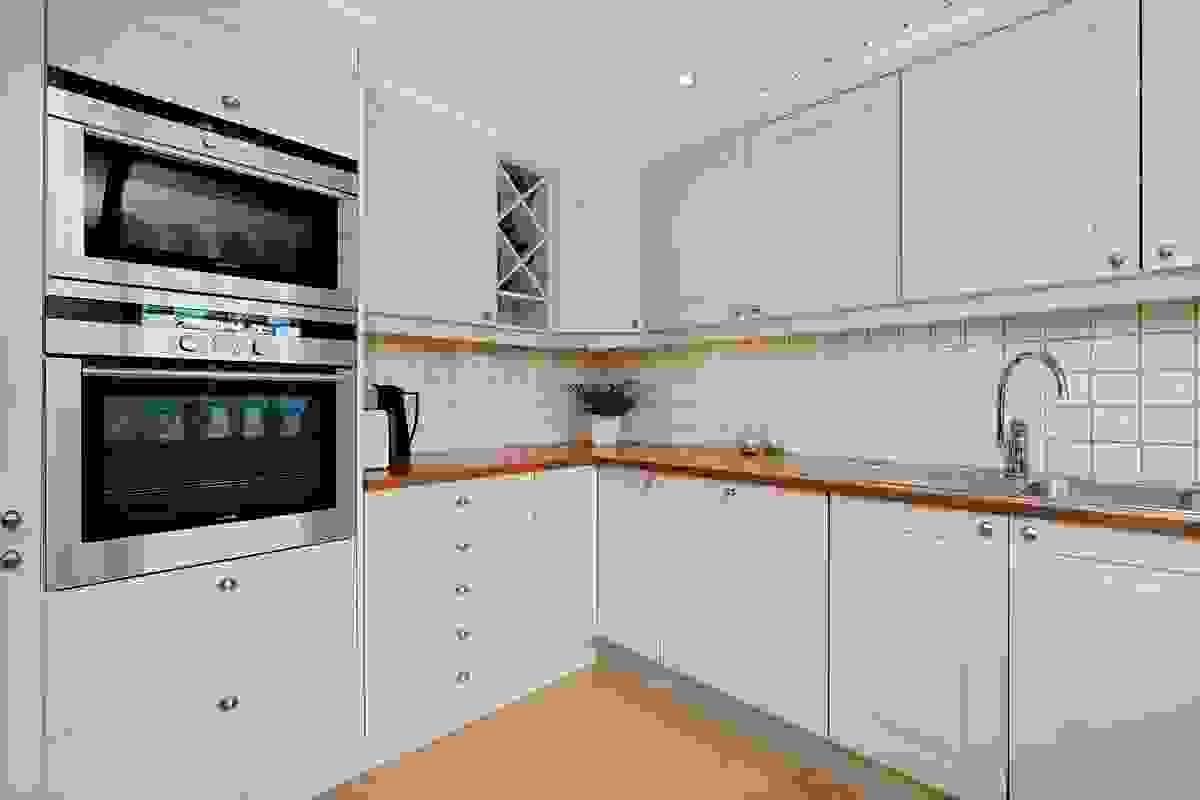 Kjøkkenet er i lyst, flott utførelse og har god skap- og benkeplass