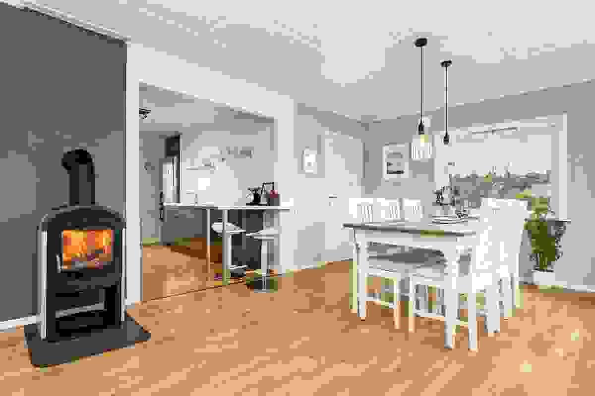 Sentralt plassert i stuearrangementet står den varmeeffektive peisovnen fra 2013.