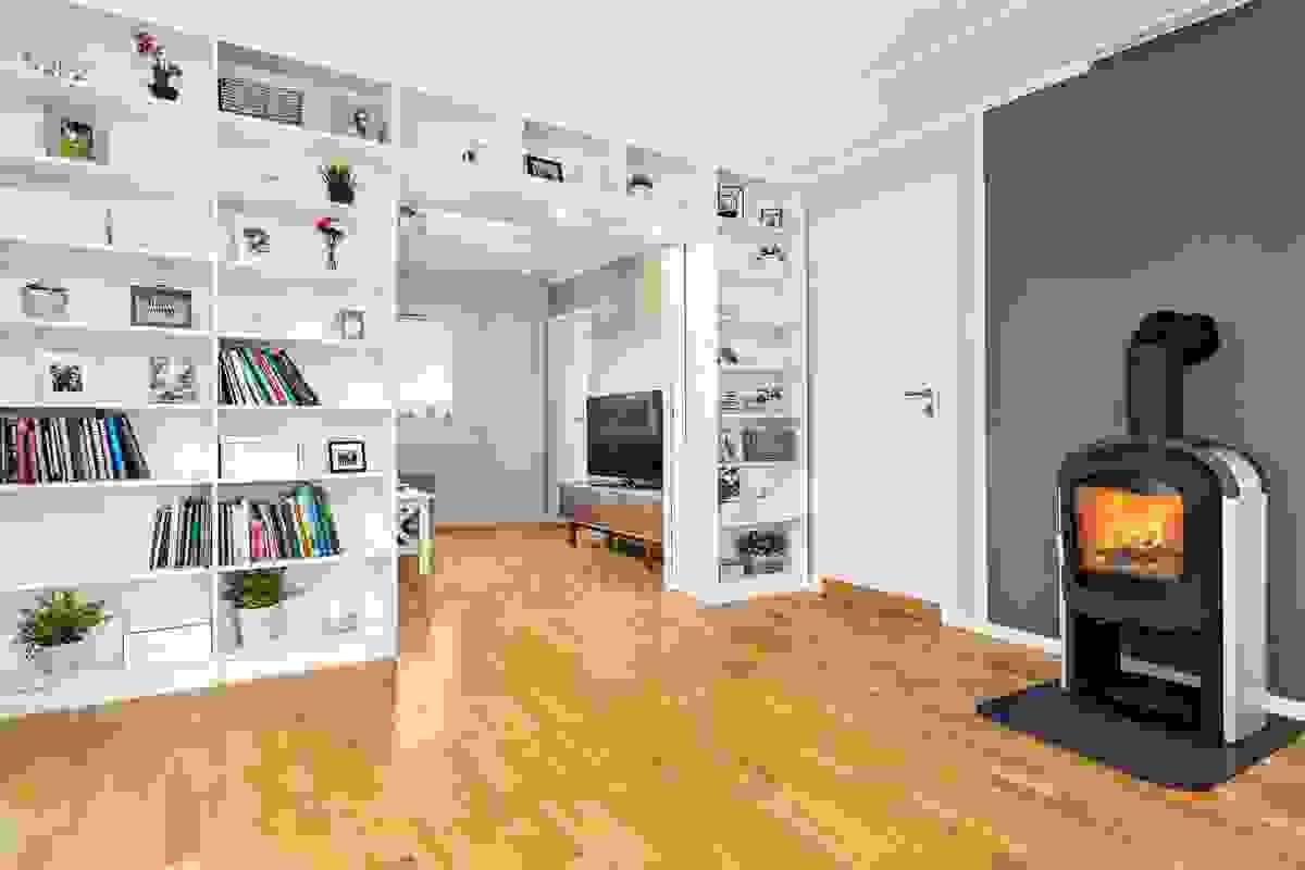 Legg merke til detaljen med plassbygget bokhylle som fyller hele veggen mellom hovedstuen og TV-stuen