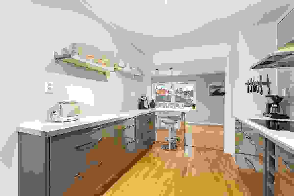 Kjøkkenet har massevis av benkeplass, og i åpningen mot stue-/spisestue er det anlagt en praktisk spisebenk som gir flott nærkontakt rommene imellom