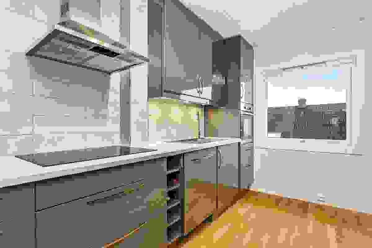 """Keramiske fliser mellom benker og overskap preger veggen i """"steke-/oppvasksonen""""."""