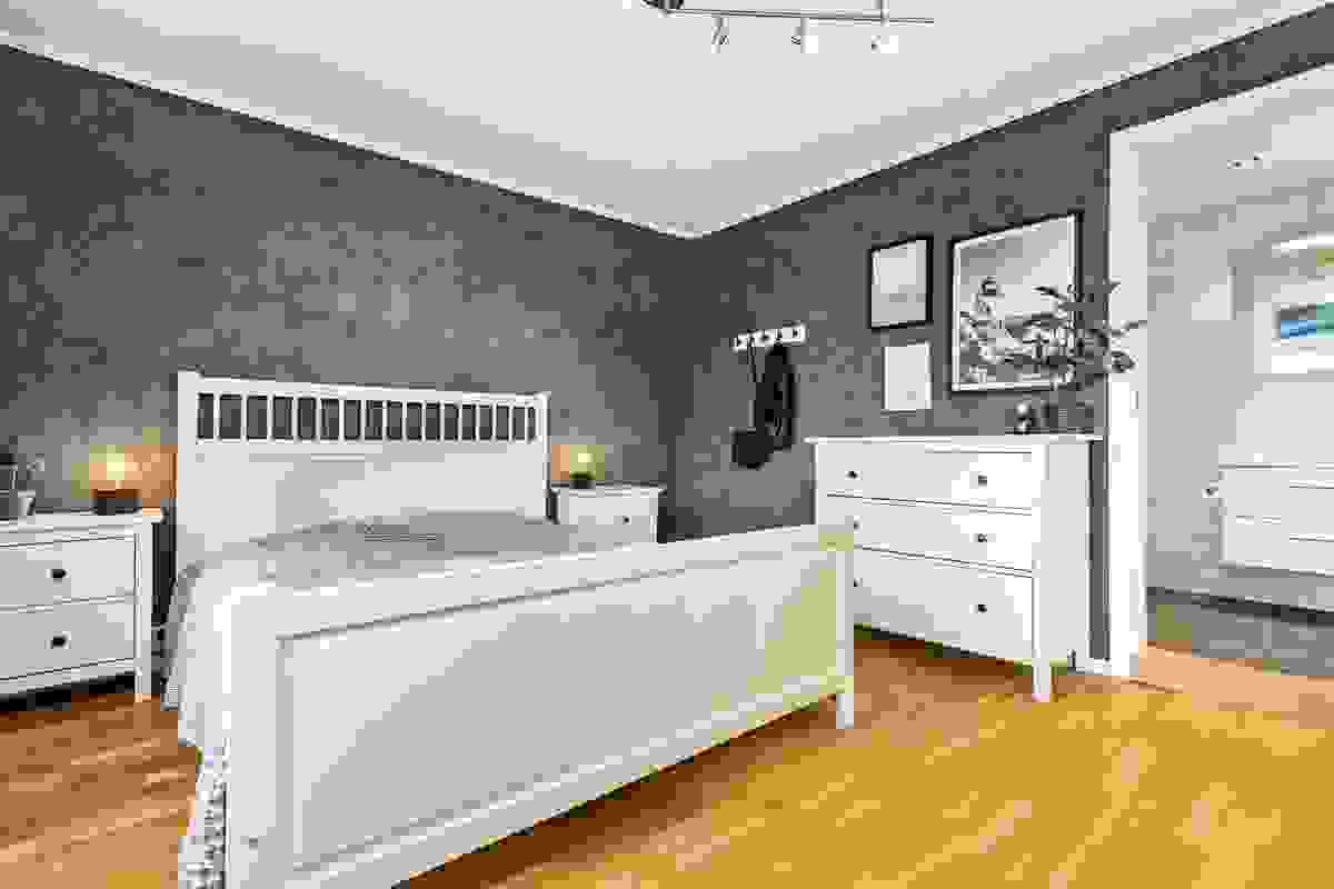 Romslig soverom med garderobe, plass til dobbelseng og direkte inngang til både baderom og TV-stue