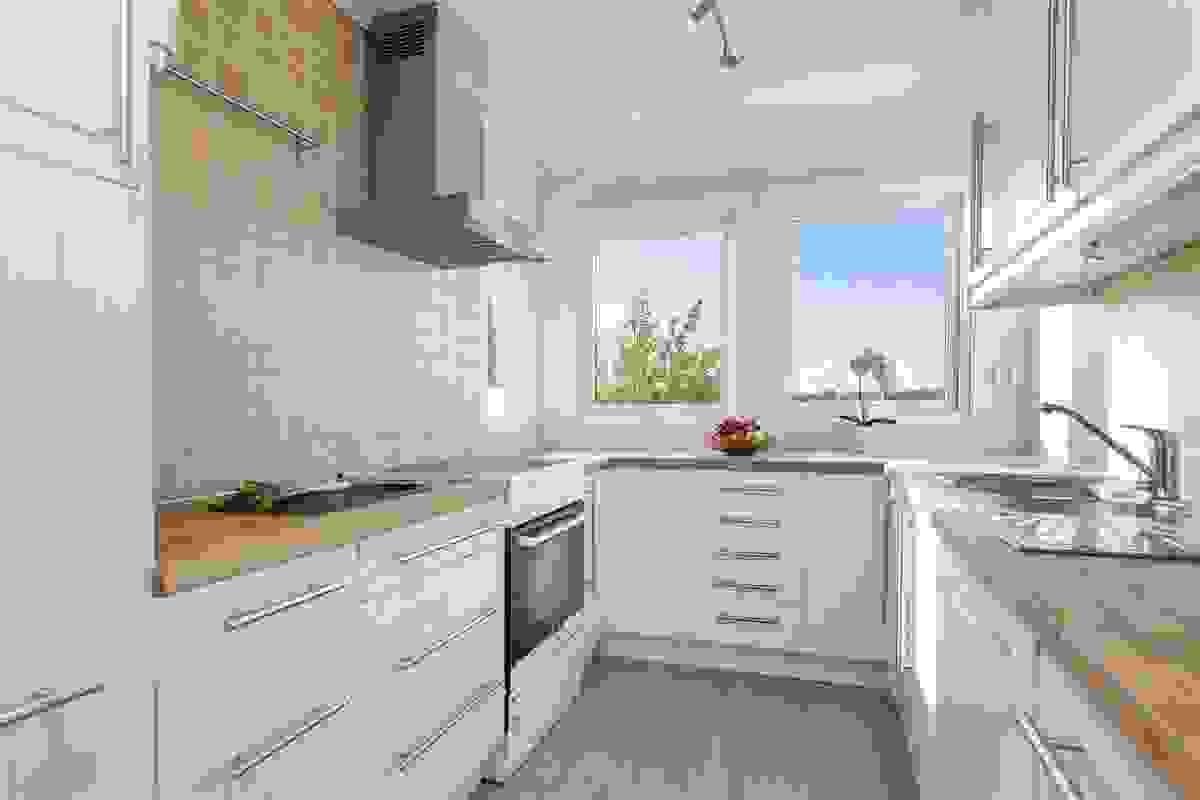 Det innbydende, lyse og innholdsrike kjøkkenet har skapplass i massevis