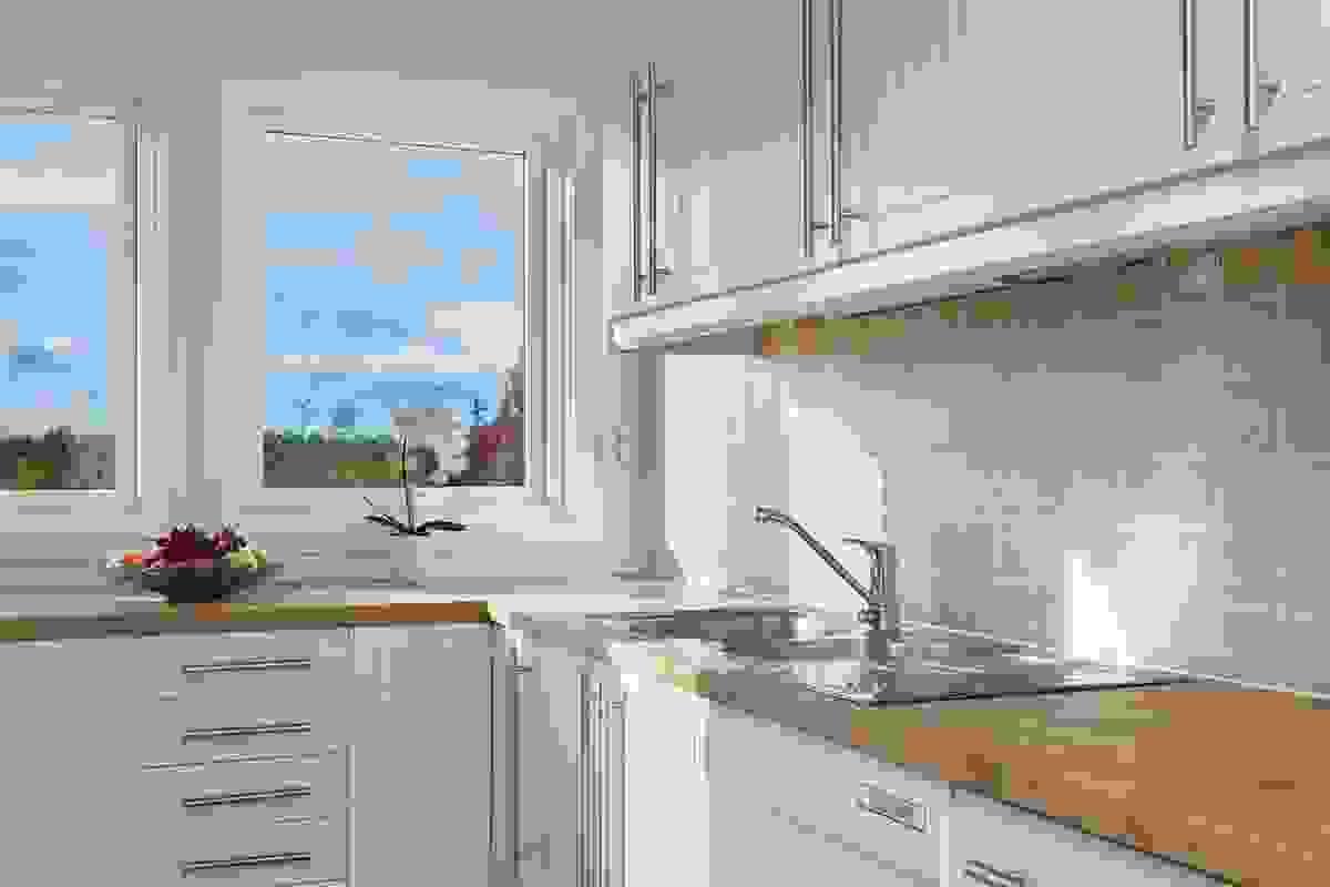Store vinduer mot vest på kjøkkenet som slipper inn massevis av lys