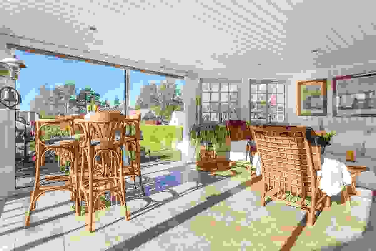 Hagestue fra 2004/2005 med flislagt gulv og glassvegger ut mot terrasse og hage