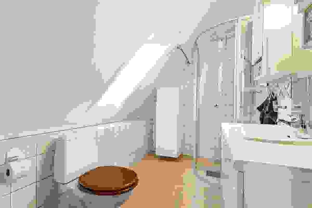 Skråtak med stort takvindu (nytt glass 2016) gir særpreg og dagslys til rommet som er innredet med nytt dusjhjørne med ovale svingdører av herdet glass fra ca. 2008