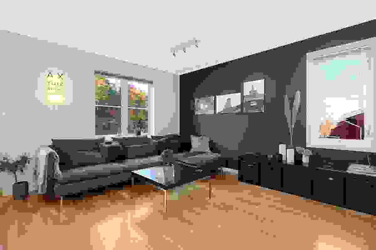 Flott kontrastvegg i samme farge som kjøkkenet i andre enden av rommet