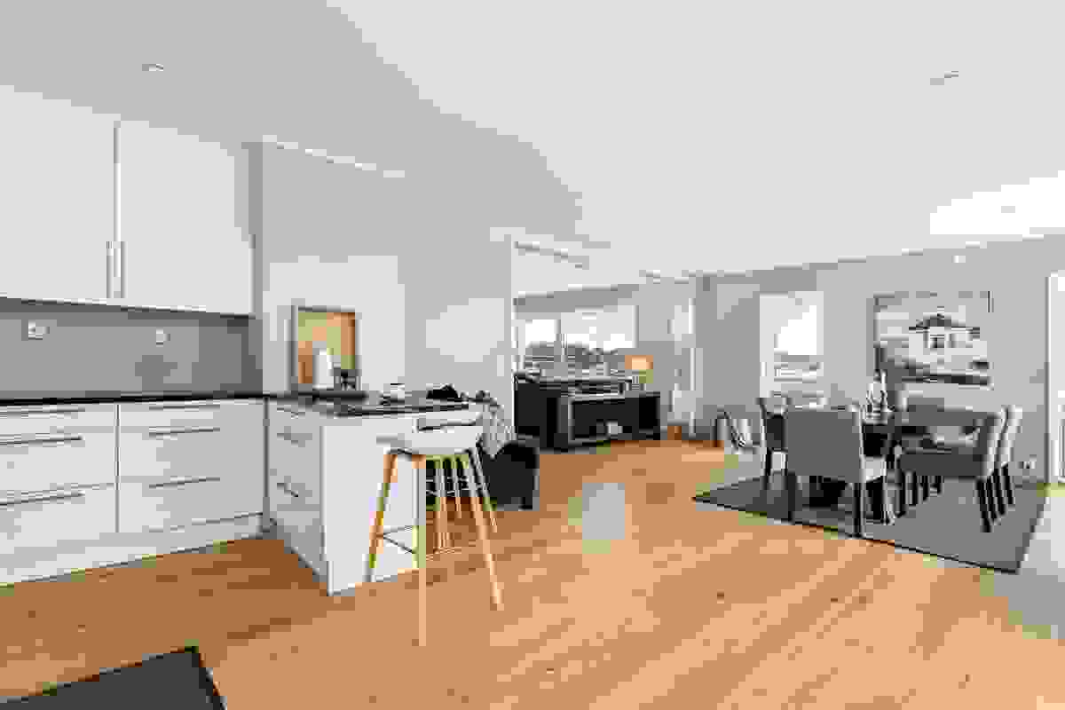 KJØKKENET ligger tilbaketrukket fra stue-/spisestue, men likevel plassert delvis åpent i fin harmoni mot leilighetens kanskje mest naturlige sted å ha spisestue