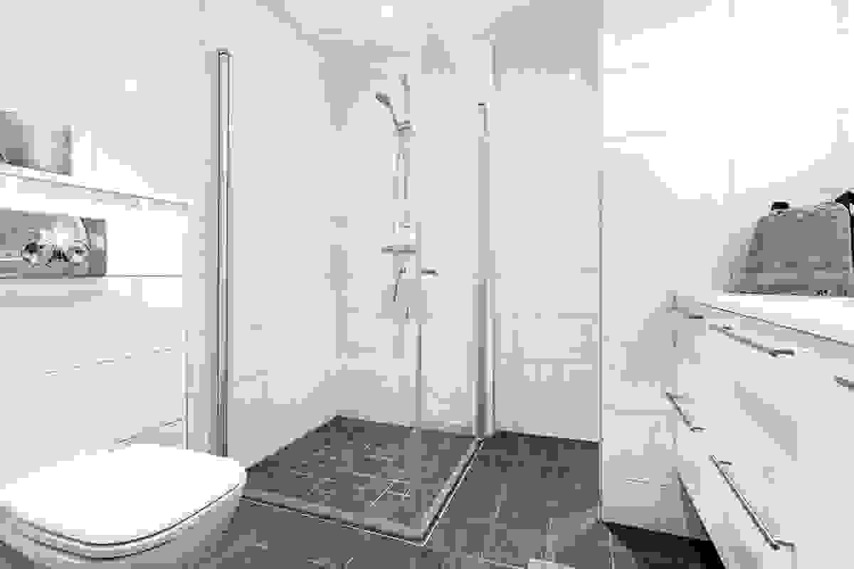 I dusjløsningene i begge rommene er det matchende fliser av mindre dimensjon enn øvrige gulvfliser og dusjvegger med glassdører i herdet glass