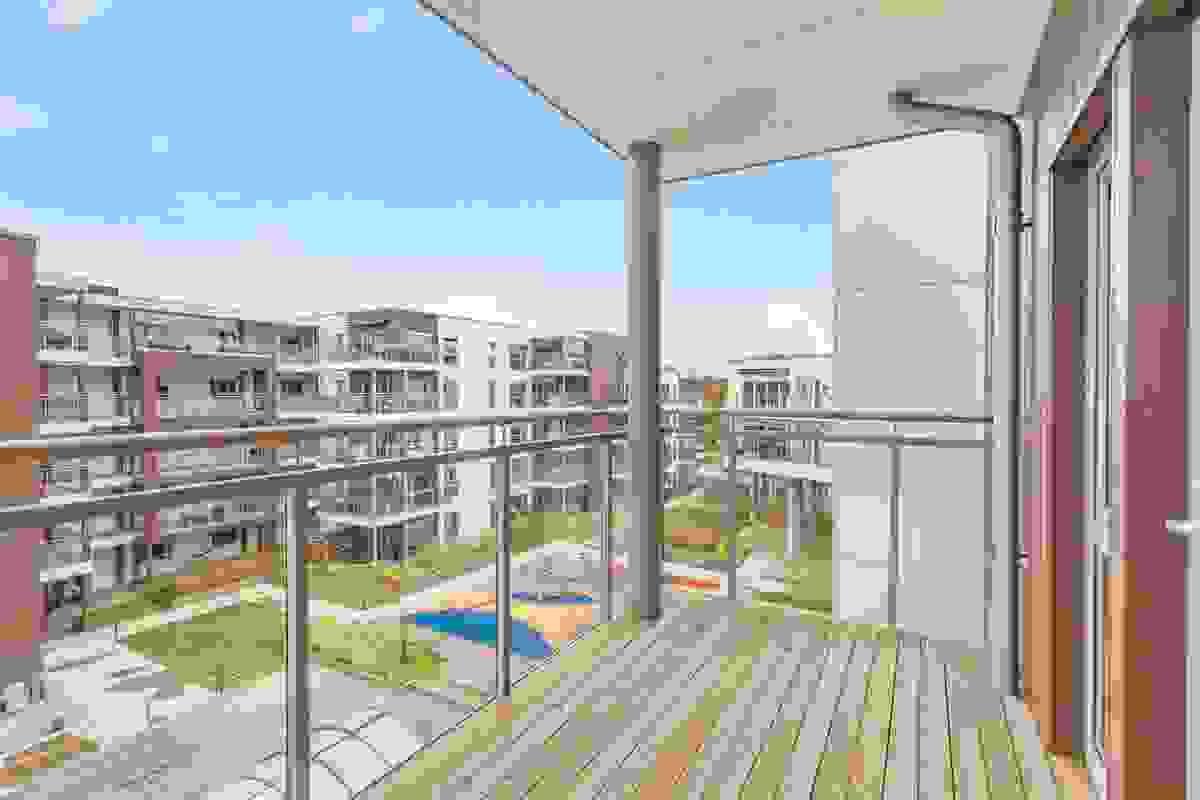 Fra kjøkkenbalkongen har man utsikt til byggets felles atrium med blant annet svømmebasseng