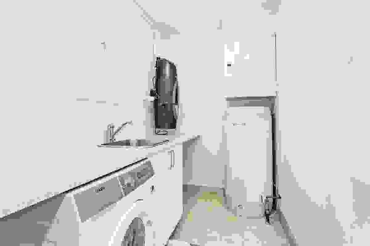 Vaskerom er praktisk innredet med bl.a. opplegg for vaskemaskin og tørketrommel, utslagsvask, brettebenk og sentralstøvsuger