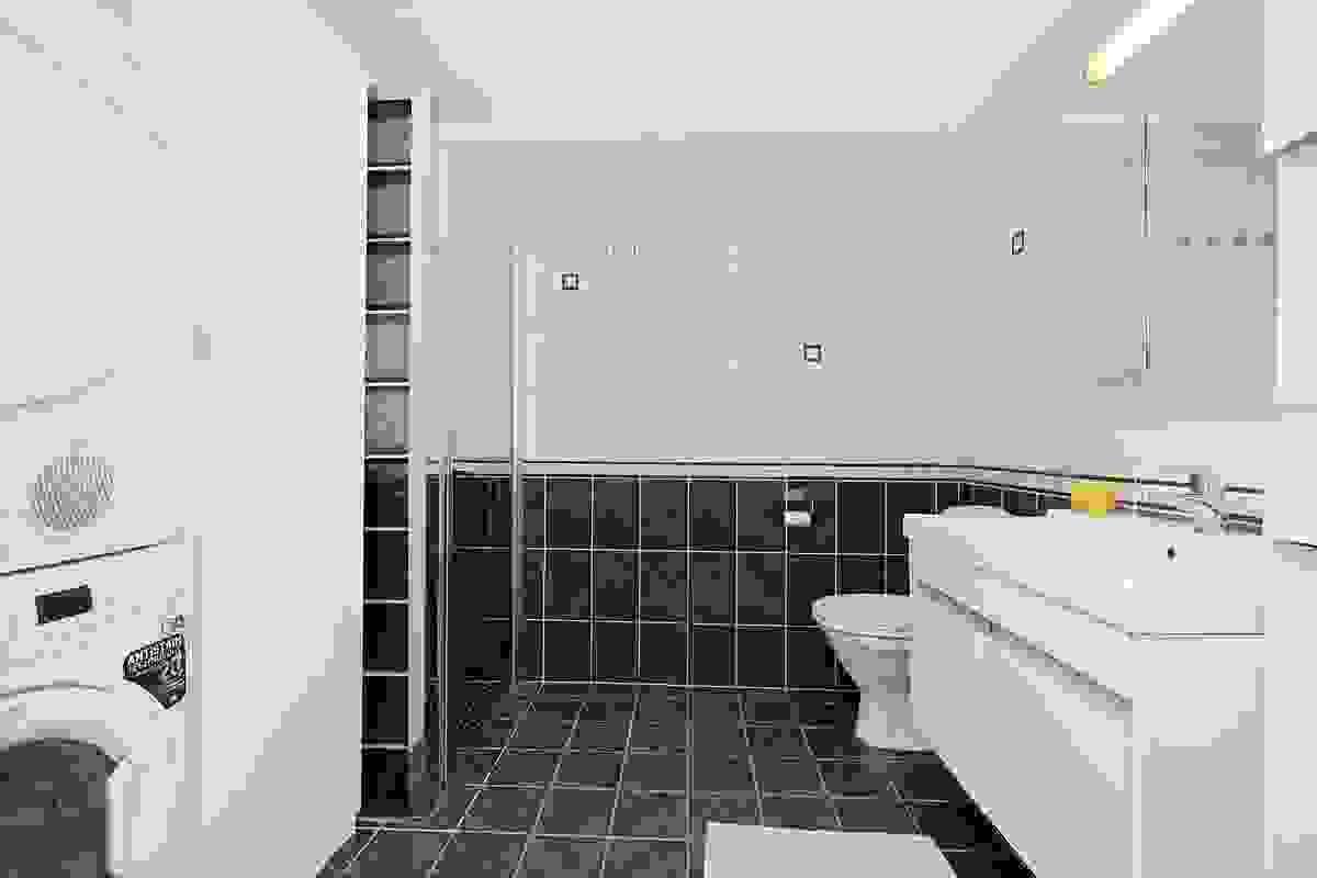 Badet inneholder bl a opplegg for vaskemaskin og høyskap