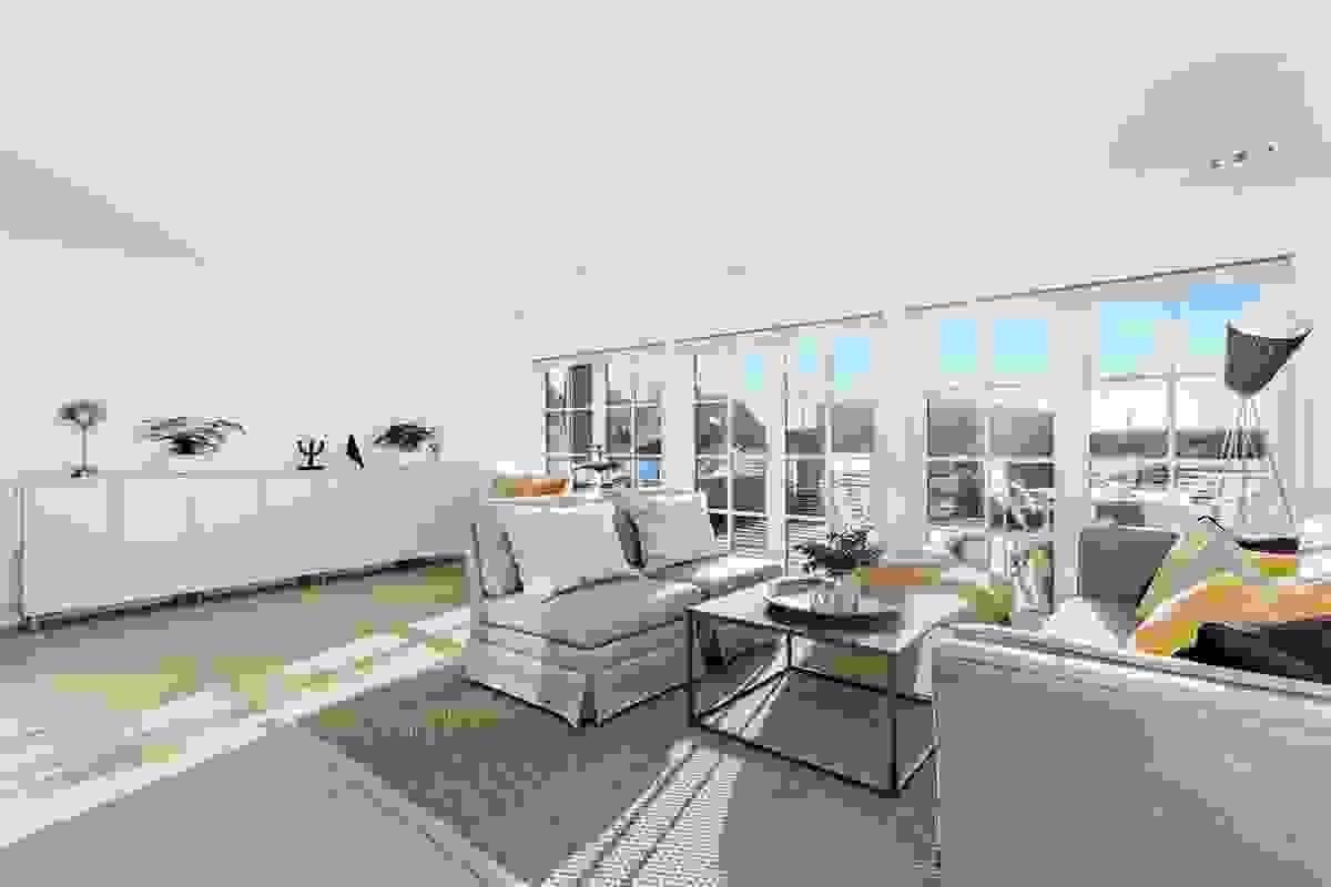 """De nye og dype vinduene mot både syd og vest blir nærmest som et """"møbel"""" i rommet og gir flott nærkontakt med hagen og hovedterrassen."""