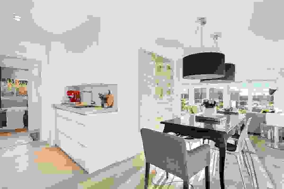 Koselig spisestue i åpen løsning med hovedstuen og kjøkkenet.