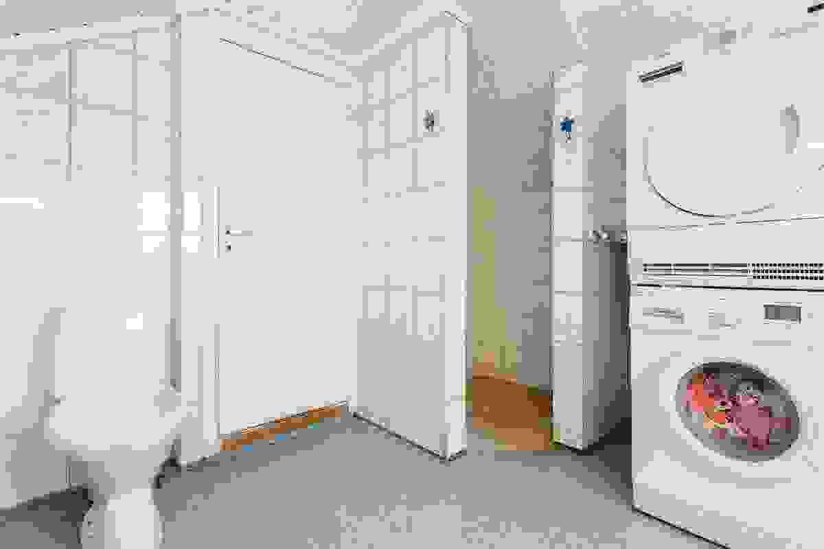 Badet inneholder dusjnisje, servant, wc, opplegg for vaskemaskin og tørketrommel, og panelovn