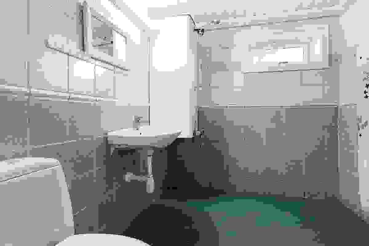 Bad i kjeller som inneholder dusj, servant, wc, panelovn og opplegg for vaskemaskin