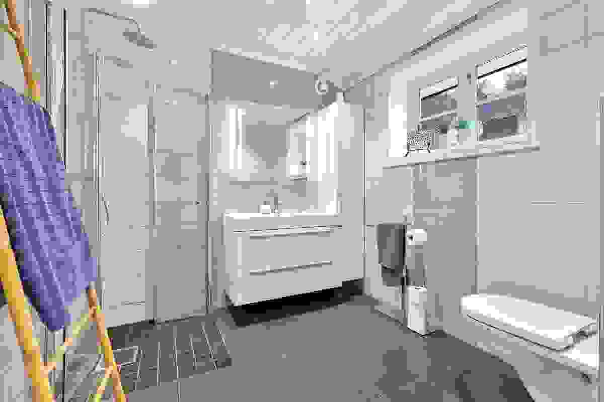 Pent flislagt bad i 2. etasje med baderomsinnredning med heldekkende servant, vegghengt wc og dusj på vegg med dusjvegger av glass