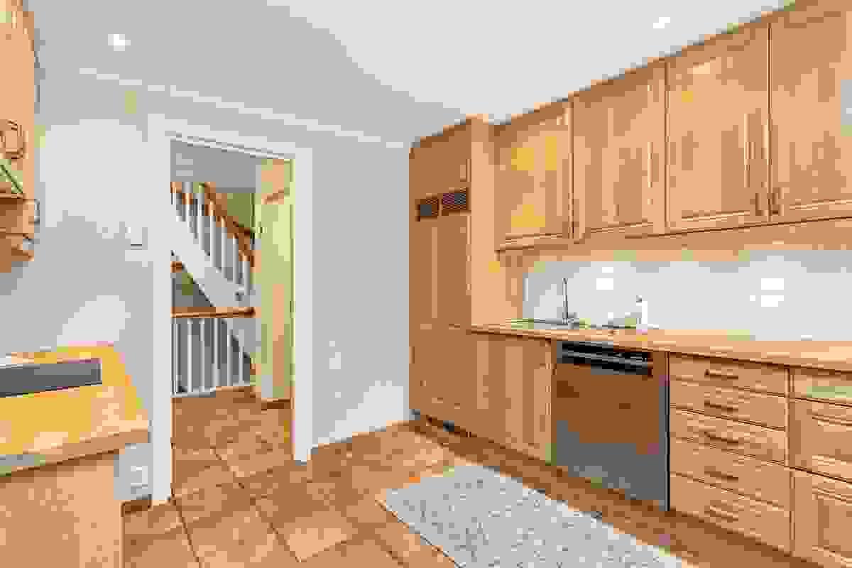 Pent tilpasset innrednng av eik med takhøye overskap, noe bruk av praktiske kolonialskuffer og godt med belysning over heltre benkeplater på begge sider av rommet.