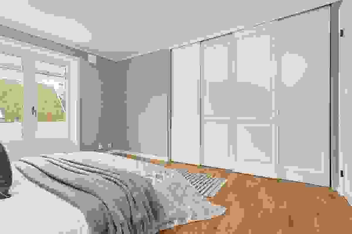 Soverommene ligger vegg-i-vegg med hverandre og begge er innredet med innbygde skyvedørsgarderober med takhøye dører