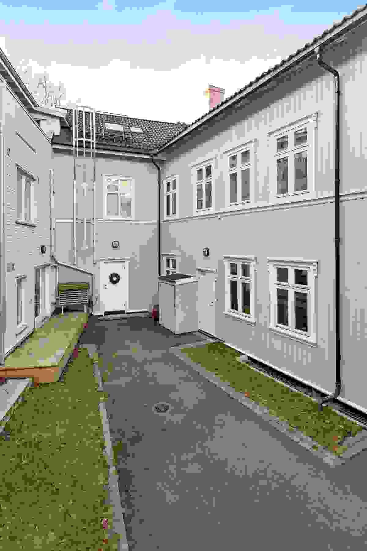 Leiligheten har inngang fra rolig bakgård, se dør til høyre midt i bildet.