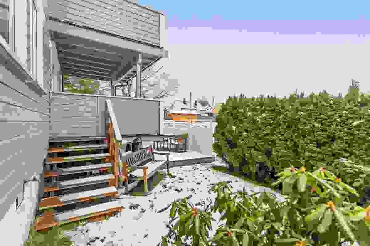 Nedenfor terrassen er en liten hageflekk og platting som denne leiligheten disponerer