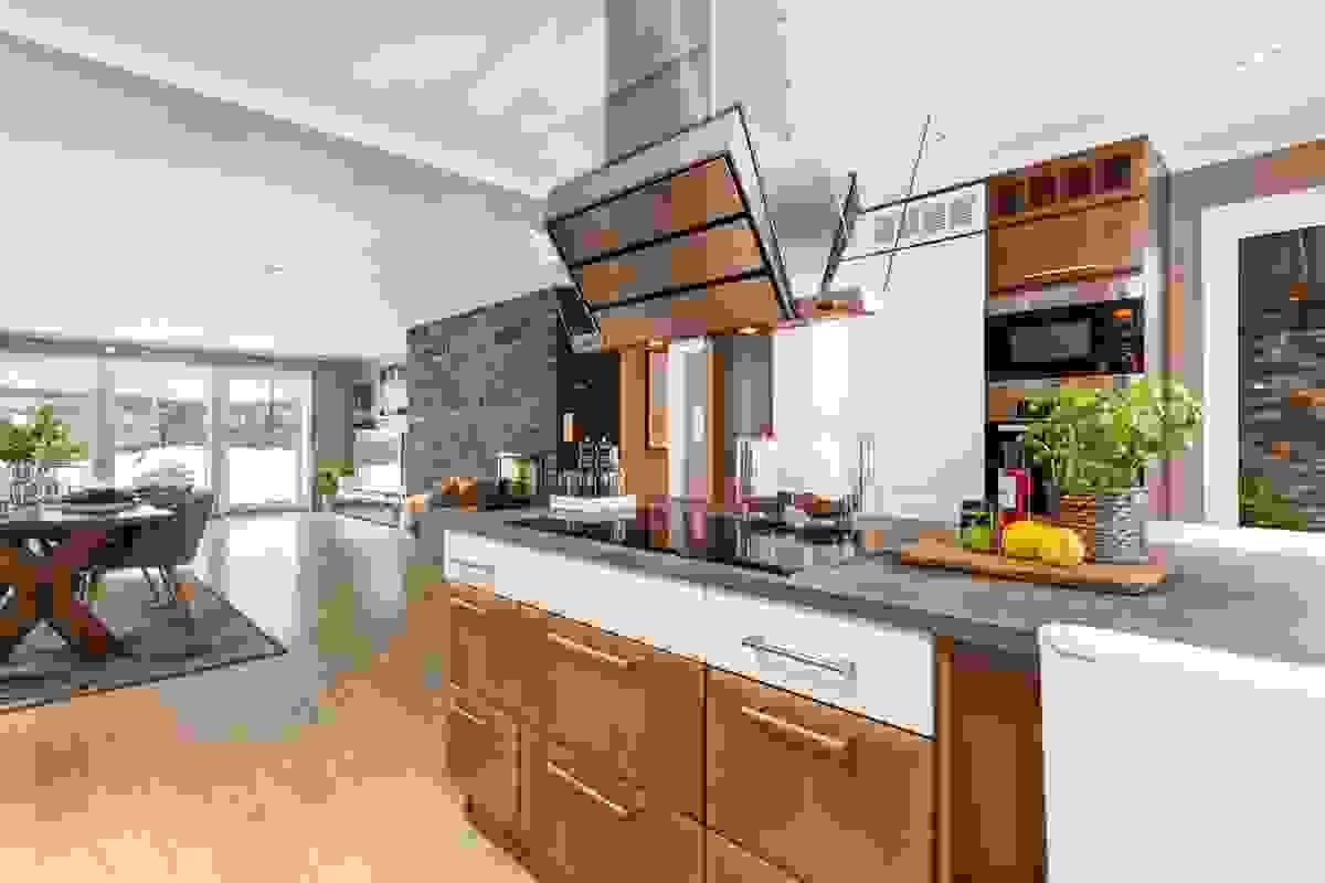 Stor kjøkkenøy med steketopp og spiseplass.