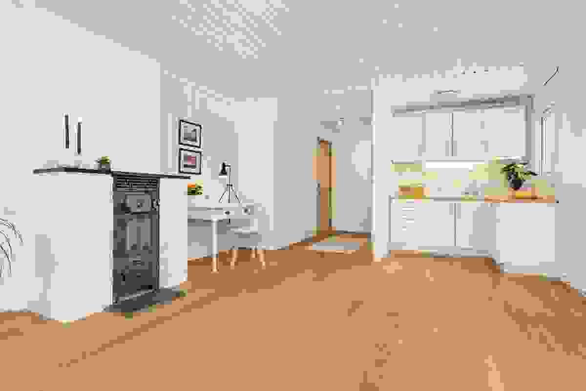 Åpen stue-/kjøkkenløsning med eldre vedovn.