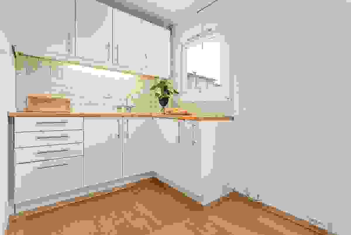 Eldre, men funksjonell kjøkkeninnredning i åpen løsning mot stua.