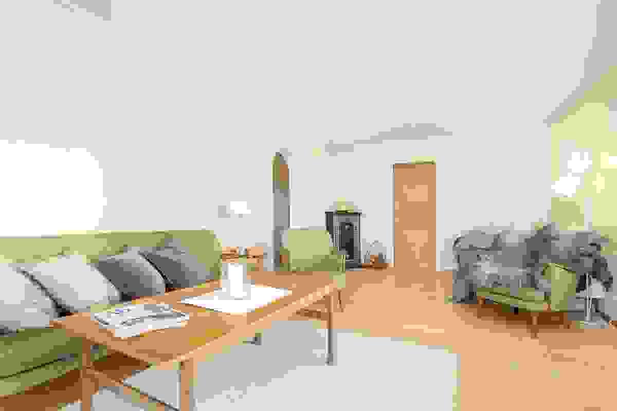 Leilighetens koselige vedkamin står sentralt plassert i et av rommets hjørner.