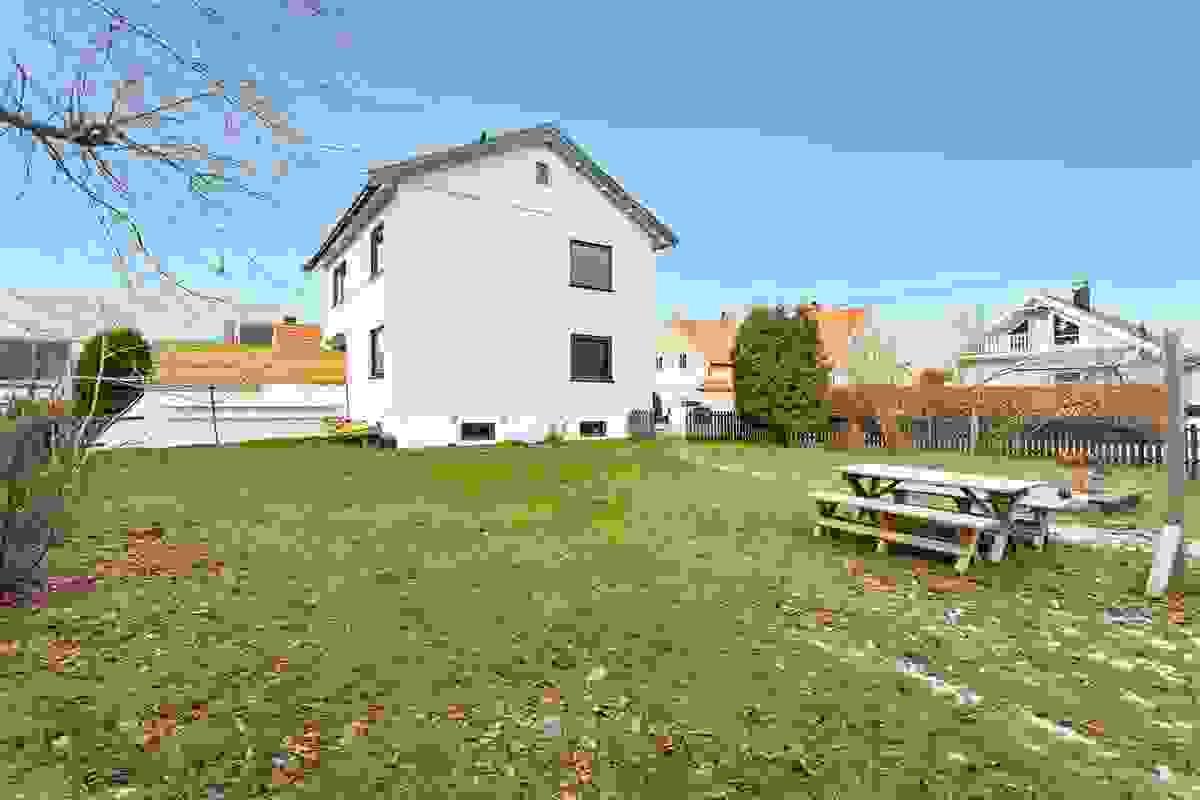 Husets plassering på tomten gir et åpent, solrikt og svært romslig hageuterom