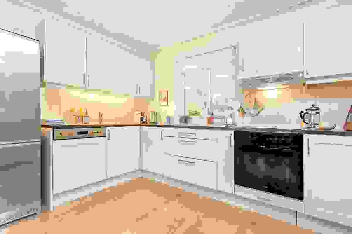 Kjøkkenet sin åpne og delvis tilbaketrukne løsning gir en fin nærkontakt med stuen