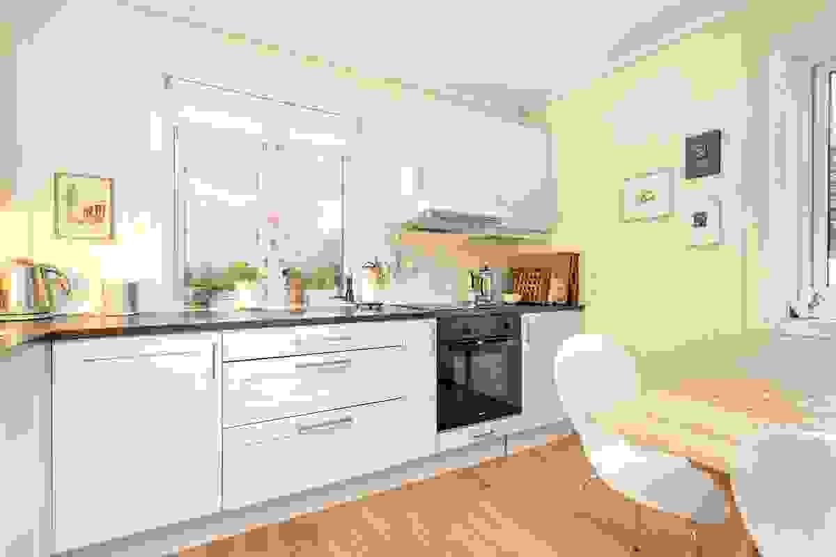 """Rommet har pent tilpasset og lys innredning med moderne """"kvadratfronter"""","""